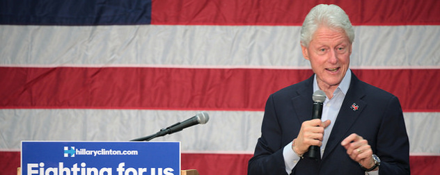 Bill Clinton speaking with a microphone in front of an American flag