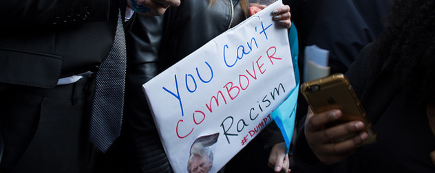 protest sign with a picture of Donald Trump and the slogan 'You can't combover racism'