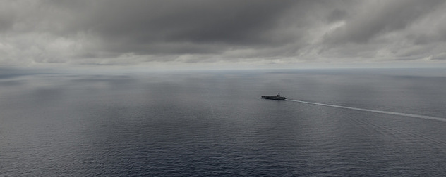 distant view of the USS Ronald Reagan on the South China Sea under a cloudy sky