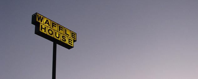 an illuminated Waffle House sign against a dawn sky