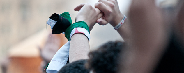 protester with raised hands wearing a Syrian flag around a wrist