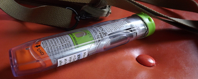 an EpiPen resting on a red leather seat next to a bag's strap