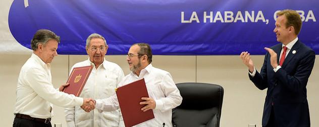 Juan Manuel Santos Calderon shakes the hand of Timoleon Jimenez while Raul Castro looks on and an observer claps