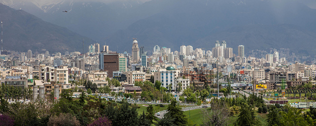 downtown Tehran, viewed against the mountains with an airplane in the distance