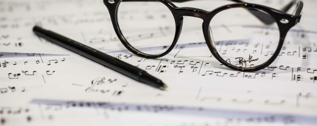eyeglasses and a ball-point pen resting on sheet music