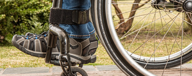 detail of person's feet and ankles in sneakers and jeans, resting on a wheelchair footrest