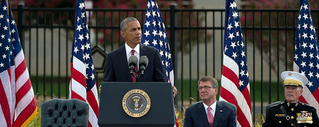 President Obama speaking at an outdoor podium in front of a row of American flags,