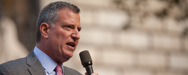 Bill de Blasio speaking outdoors with a hand-held microphone
