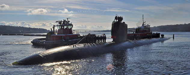Two tugboats push the naval submarine the USS Alexandria into a pier