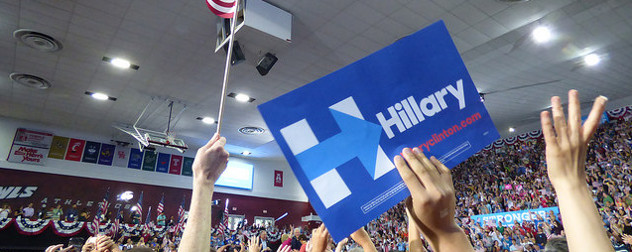 Hillary Clinton campaign sign held aloft in front of a crowd at a rally