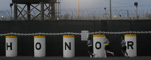 3 members of the U.S. Army run in front of the Honor Bound sign at Guantanamo's Camp Delta