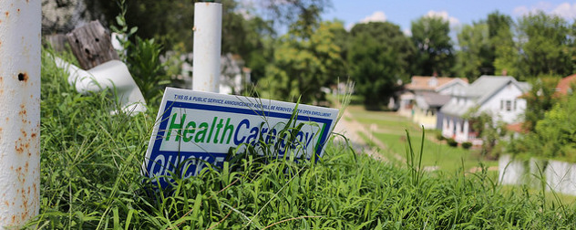yard sign advertising HealthCare.gov, obscured by tall grass