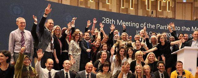 delegates to the 28th Meeting of Parties to the Montreal Protocol waving and smiling