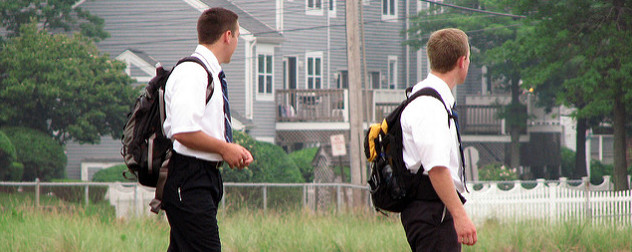 two young men in short-sleeve shirts and ties, with backpacks, turned away from the camera