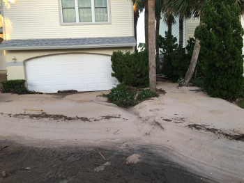 beach property's driveway filled with sand