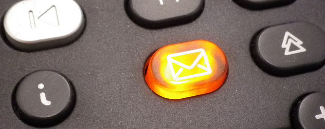 detail of orange illuminated voicemail button on a phone