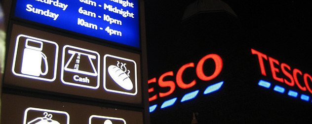 illuminated Tesco sign including icons indicating gasoline, ATM and bakery services are offered
