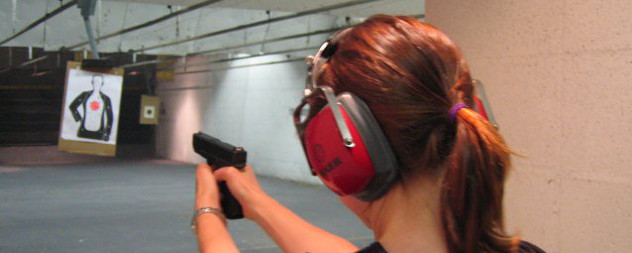 person with a ponytail, viewed from behind, firing a Glock 23 at a gun range