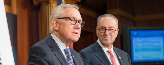 Harry Reid speaks at a podium while Chuck Schumer looks on