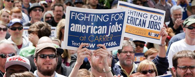 protesters at a rally, one holding a sign that reads Fighting For American Jobs at Carrier