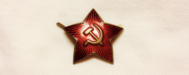 anitque Soviet pin in the shape of a star with a hammer and sickle design