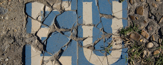 cracked sign with the white letters EU on a blue background