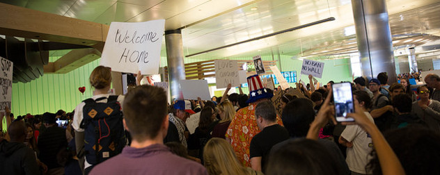 Protesters against Trump's executive order on immigration hold signs that read 'Welcome Home,' 'No Ban, No Wall,' and 'Love Conquers All'