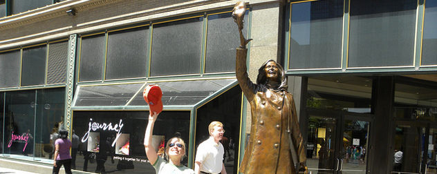 tourist tossing a baseball cap into the air next to the statue of Mary Richards in Minneapolis