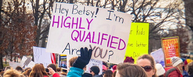 protester holding a sign that reads 'Hey Betsy! I'm highly qualified - are you?'