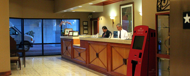 two employees at a reception desk of a San Jose-area Crowne Plaza hotel