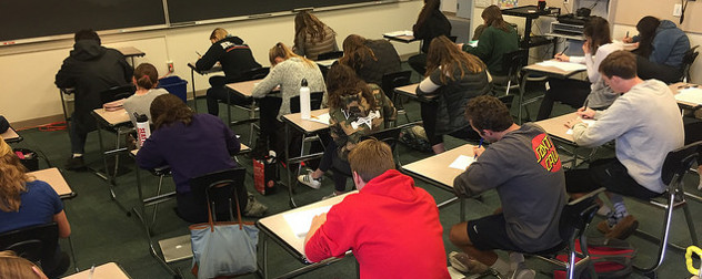 students seated at desks, working on exams, seen from behind