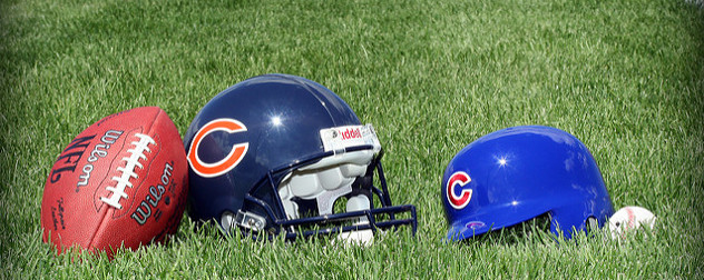 a football, a Chicago Bears helmet, a Chicago Cubs batting helmet, and a baseball resting on grass