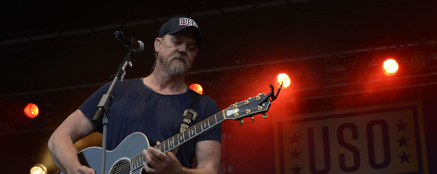 Trace Adkins plays guitar in front of a USO banner