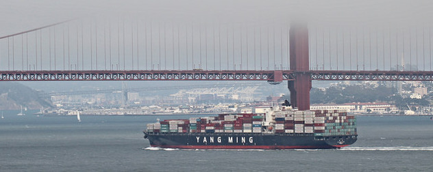cargo ship passing by the Golden Gate Bridge on a foggy day