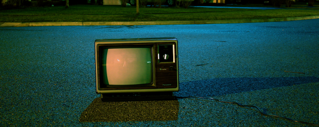 vintage TV sitting in a street at night