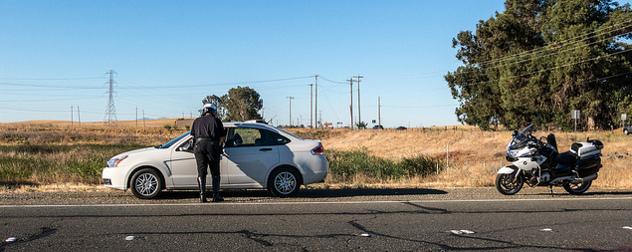 highway patrolmen speaking to a motorist in their vehicle on the shoulder