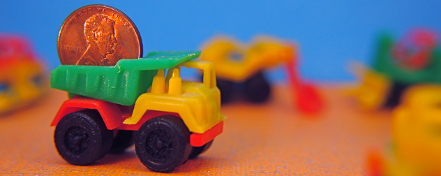 tiny toy dump truck carrying a penny