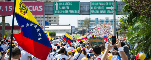 protesters with flags and signs march on the Palace of Justice in Maracaibo, Venezuela