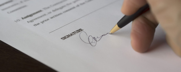 hand signing a legal document with a ballpoint pen