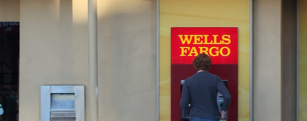 a person at a Wells Fargo ATM on a street