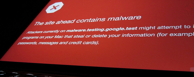 laptop screen displaying malware warning on red background