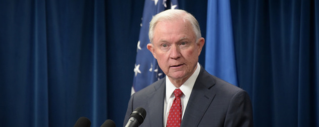 Jeff Sessions speaking at a podium in front of an American flag and a blue curtain