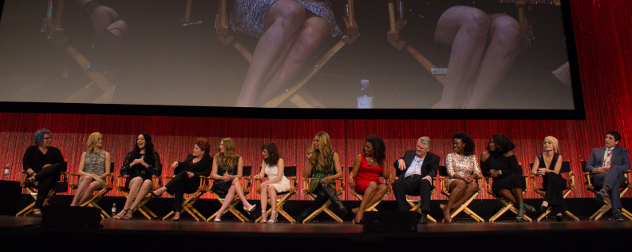 cast members of 'Orange Is the New Black' seated across a stage with a large screen behind them