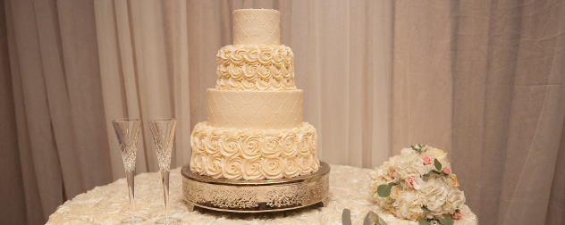 white wedding cake on a table with two champagne flutes