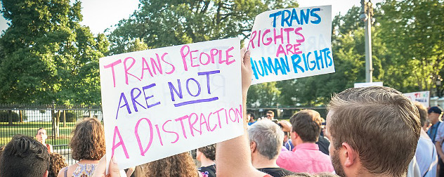 protest signs reading 'Trans People Are Not A Distraction' and 'Trans Rights Are Human Rights'