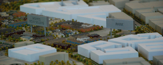 miniature neighborhood model with signs reading 'Park' and 'Homes Now Selling'