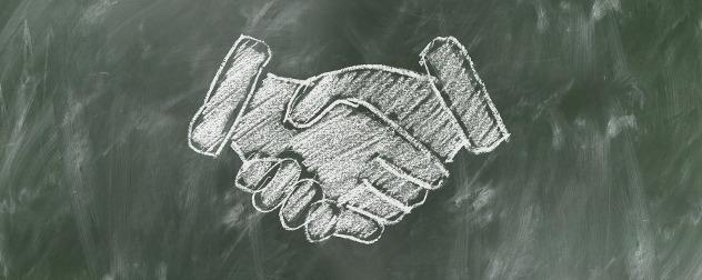 chalk drawing of a handshake on a blackboard
