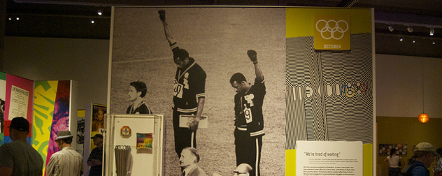 museum display featuring Tommie Smith and John Carlos raising their fists at the 1968 Olympic Games