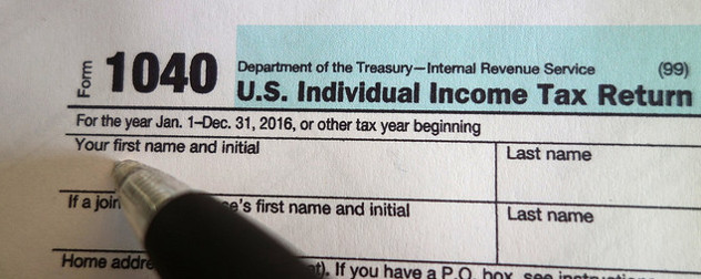 pen poised over a blank IRS Form 1040 for 2016