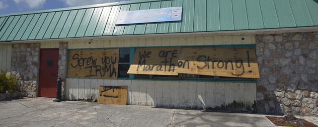 boarded-up storefront with the spraypainted message 'Screw you, Irma. We are Marathon strong!'